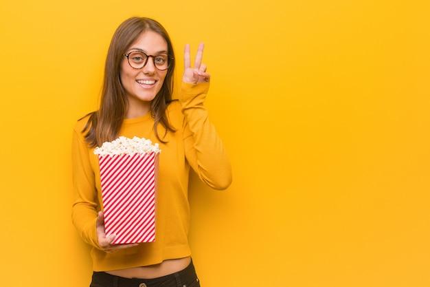 Молодая счастливая женщина делает жест победы