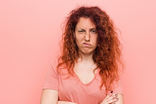 皮肉な表情でカメラで見て不幸な若い自然で本物の赤毛の女性。