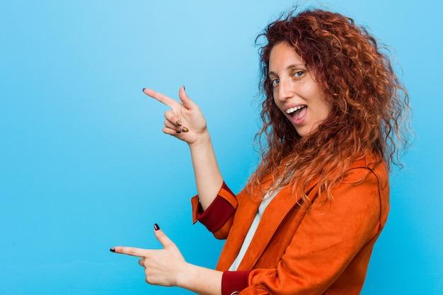 若い赤毛のエレガントな女性は、人差し指を指さして興奮しています。