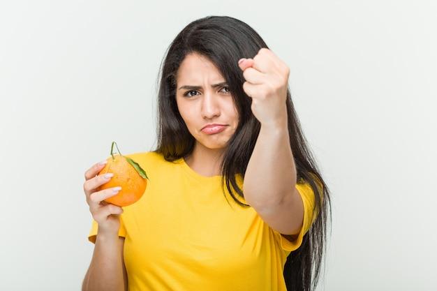 オレンジを示す拳を保持している若い女性