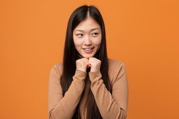 Молодая красивая китаянка держит руки под подбородком, счастливо смотрит в сторону