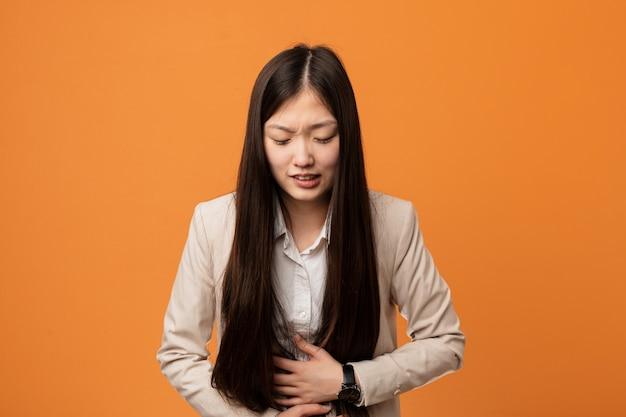 若いビジネス中国人女性の病気、腹痛に苦しむ