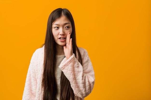 パジャマの若い中国人女性が秘密のホットブレーキニュースを言って、よそ見