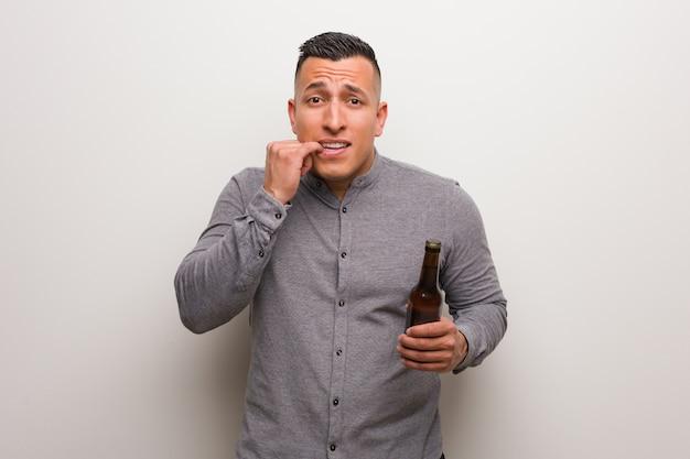 Молодой латинский мужчина держит пиво кусая ногти, нервный и очень взволнованный