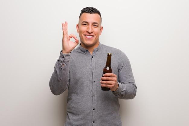 Молодой латинский мужчина держит пиво веселым и уверенным делает хорошо жест