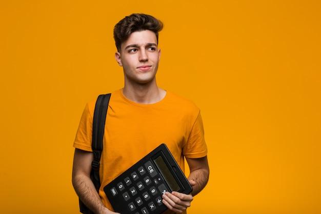 Молодой студент мужчина держит калькулятор, кусая ногти, нервный и очень взволнованный