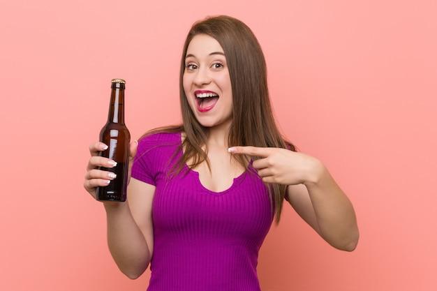Молодая кавказская женщина держа бутылку пива