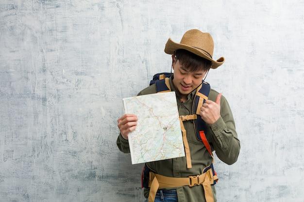 笑顔と親指を上げる地図を持って若い中国人探検家の男