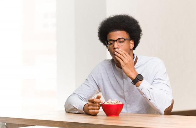 Молодой человек завтракает усталым и очень сонным