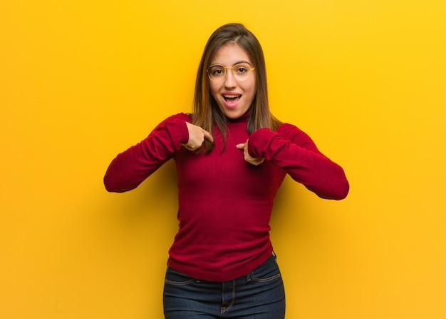 驚いた若い知的な女性は、成功と繁栄を感じます