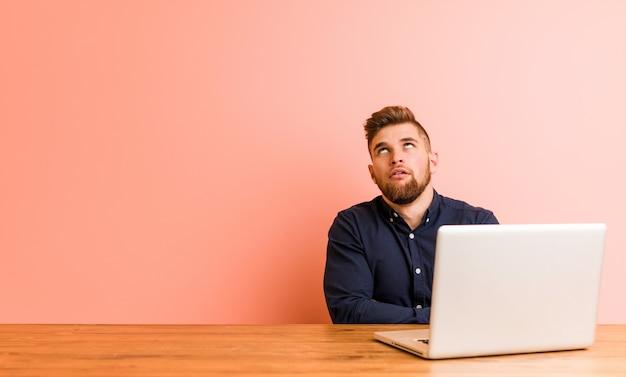 Молодой человек, работающий с его ноутбуком устал от повторяющихся задач