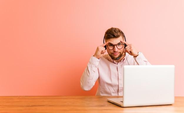 Молодой человек, работающий в колл-центре, сосредоточен на задаче, удерживая его указательными пальцами, указывая головой