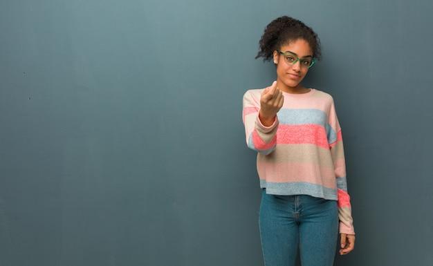 来て誘う青い目を持つ若いアフリカ系アメリカ人の女の子