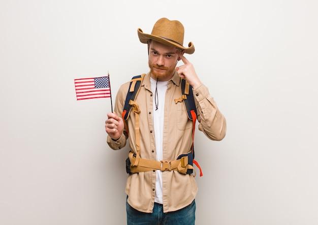 Молодой рыжий исследователь человек думает о идее, держа флаг сша