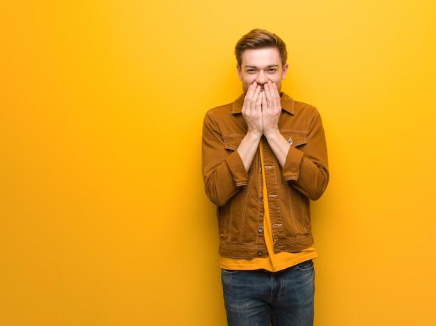 Рыжий молодой человек смеется о чем-то, прикрывая рот руками