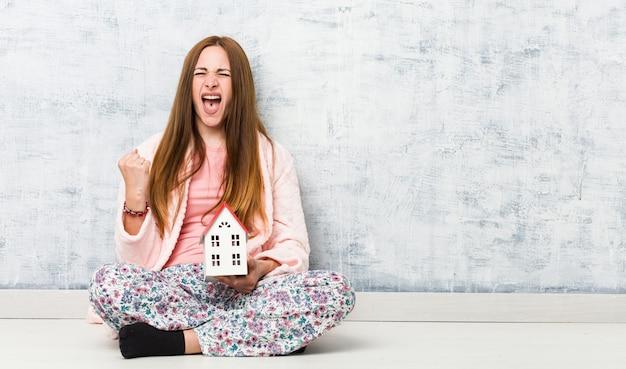 Молодая женщина держит значок дома аплодисменты беззаботный и взволнован