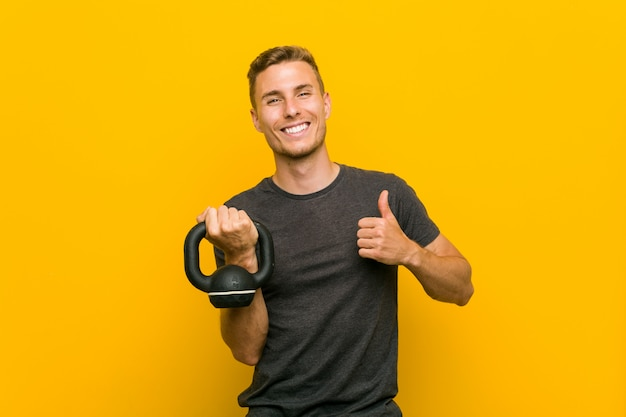 若い男笑顔と親指を上げるダンベルを保持