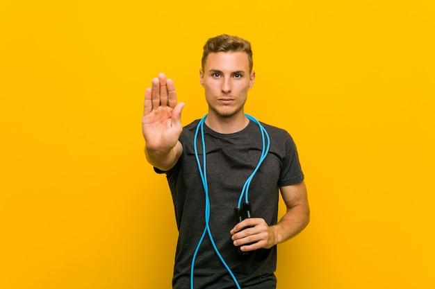 若い男が一時停止の標識を示す差し出された手で立っている縄跳びを保持