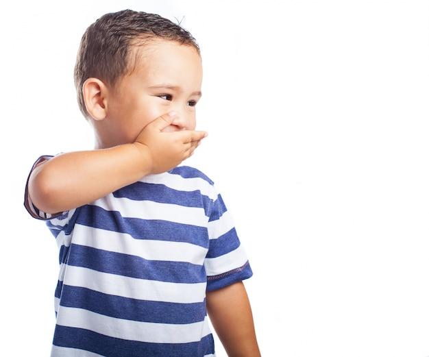 笑いながら、彼の口を覆う小さな男の子
