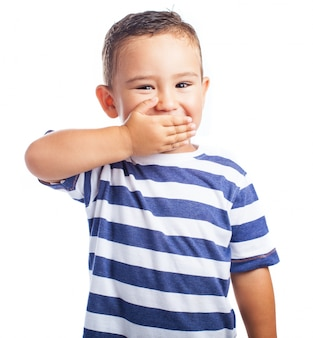 Маленький мальчик, прикрывая рот, смеясь