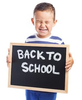 「学校に戻って」というメッセージと黒板に泣いて小さな男の子