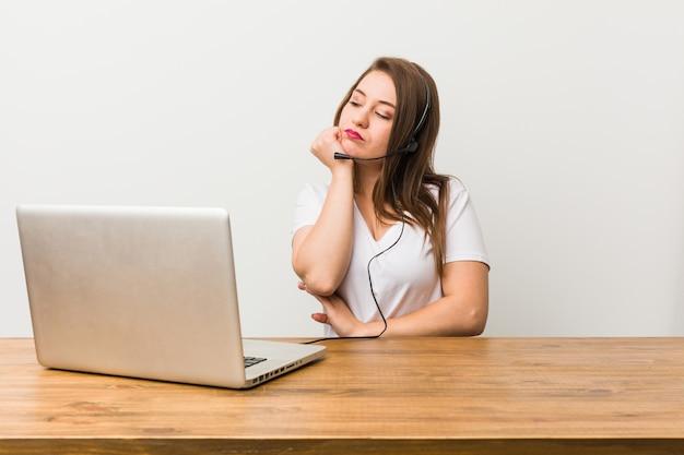 コピースペースを見て悲しいと物思いにふける感じの若いテレマーケティング女性。