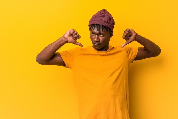 黄色の背景にラスタスを身に着けている若い黒人男性は、誇りと自信を持っていると感じています。