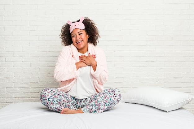 Молодая афро-американская женщина в пижаме кровати нося имеет дружелюбное выражение, отжимая ладонь к груди. концепция любви