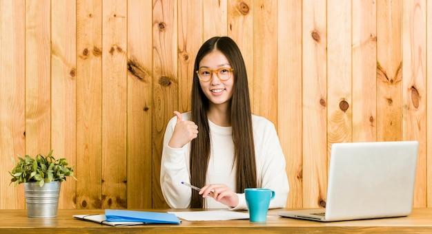 笑顔と親指を上げる彼女の机で勉強して若い中国人女性