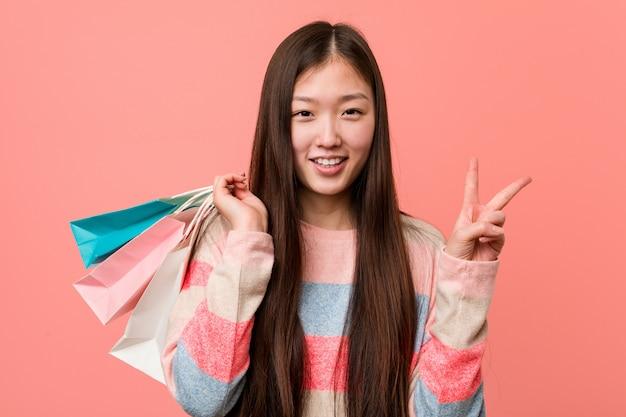 Молодая азиатская женщина держа номер два хозяйственной сумки показывая с пальцами.