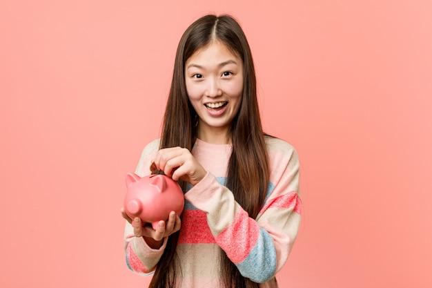貯金を保持している若いアジア女性
