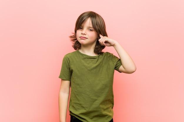 Мальчик указывая висок с пальцем, думая, сфокусированный на задаче.