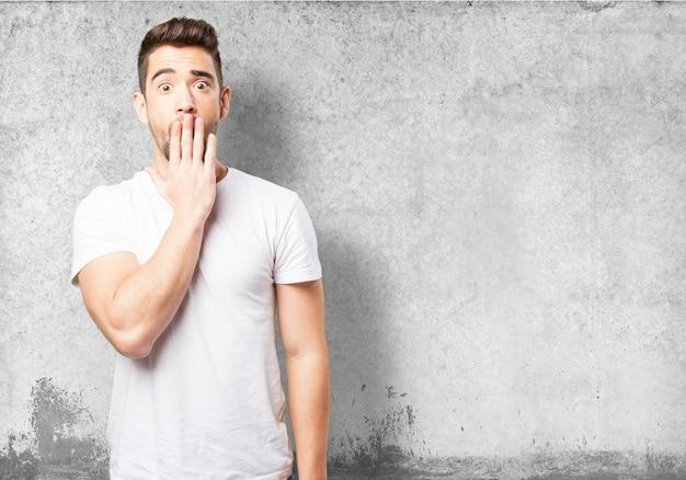 Человек, охватывающий его рот одной рукой
