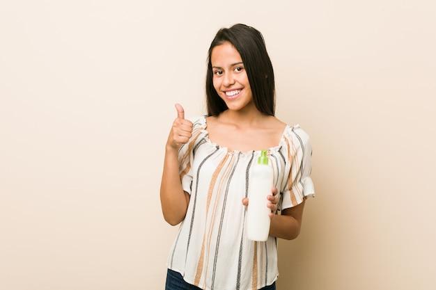 笑顔と親指を上げるクリームボトルを保持している若いヒスパニック系女性