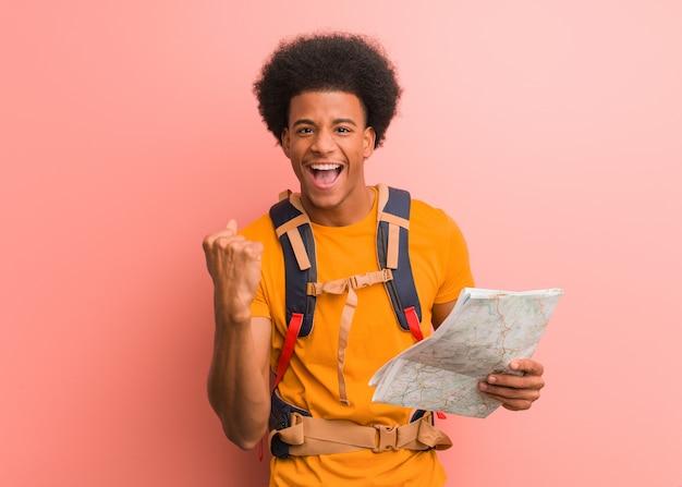 驚いてショックを受けた地図を持って若いアフリカ系アメリカ人エクスプローラー男