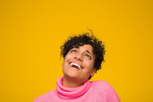 Молодая афро-американская женщина нося розовый свитер ослабила и счастливый смеяться над, шея протянула показывать зубы.