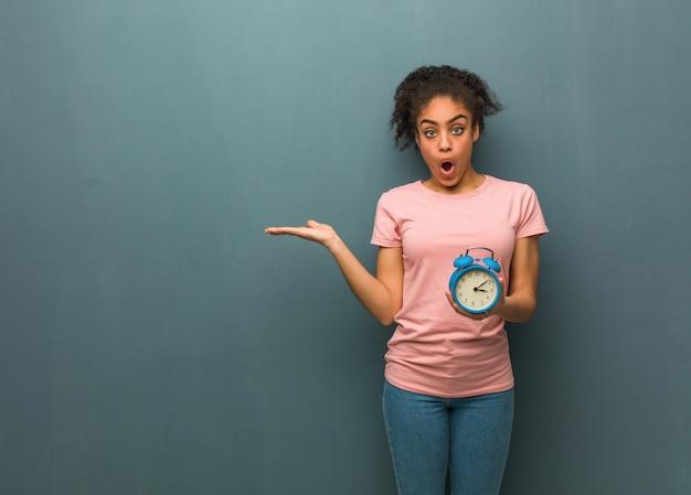 手のひらに何かを保持している若い黒人女性。彼女は目覚まし時計を持っています。