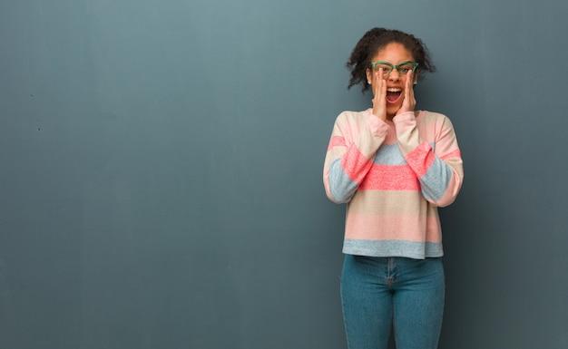 正面に幸せな何かを叫んでいる青い目を持つ若いアフリカ系アメリカ人の女の子