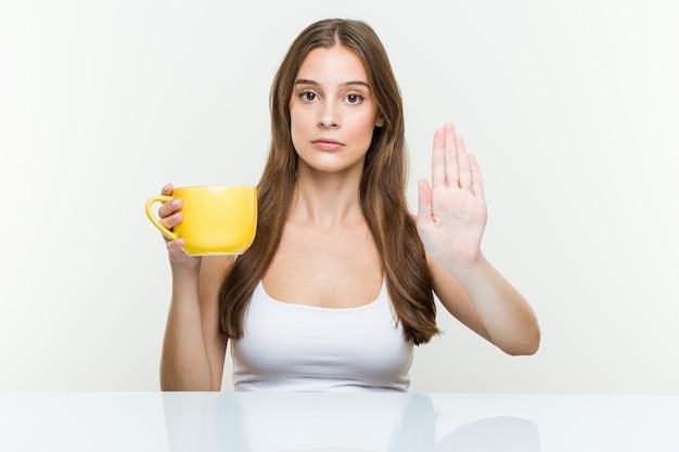 Молодая кавказская женщина держа чашку стоя с протягиванной рукой показывая знак стопа, предотвращая вас.