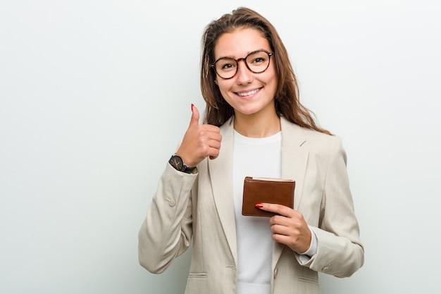 笑顔と親指を上げる財布を保持している若いヨーロッパビジネス女性