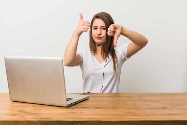 親指と親指を示す若いテレマーケティング女性、難しい選択