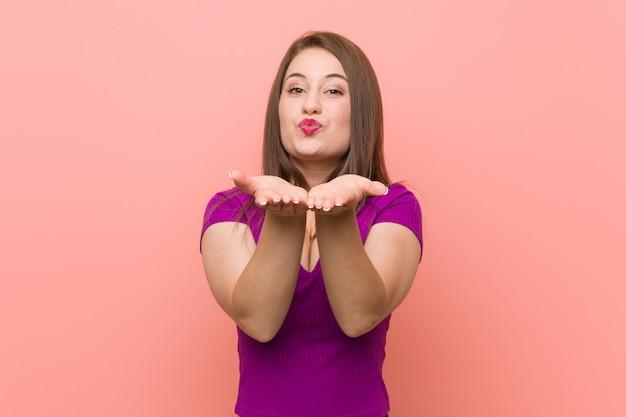 Молодая испанская женщина на розовой стене складывает губы и держит ладони, посылает воздушный поцелуй.