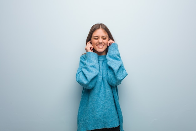 手で耳を覆う青いセーターを着ている若いきれいな女性