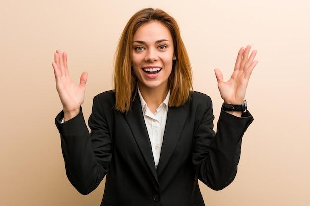 嬉しい驚き、興奮して手を上げる若い白人ビジネス女性。