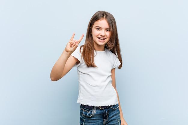 Милая девушка показывает жест рога как революция.
