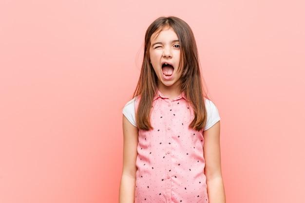 Милая маленькая девочка подмигивает, веселая, дружелюбная и беззаботная.
