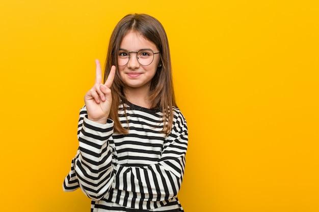 Маленькая кавказская милая девушка показывая номер два с пальцами.