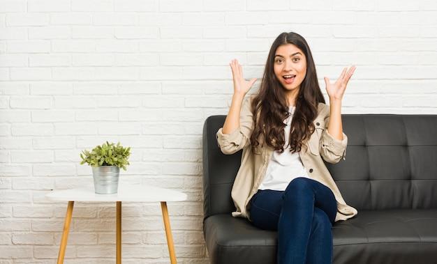 楽しい驚きを受けて、興奮して手を上げる若いアラブ女性座っているソファ。