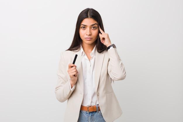 Молодая арабская женщина держа кредитную карточку указывая его висок с пальцем, думая, сфокусировала задачу.