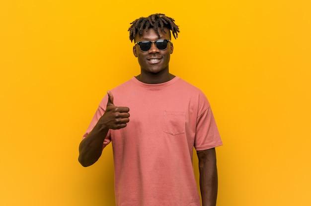 笑みを浮かべて、親指を上げるサングラスを着ている若いカジュアルな黒人男性